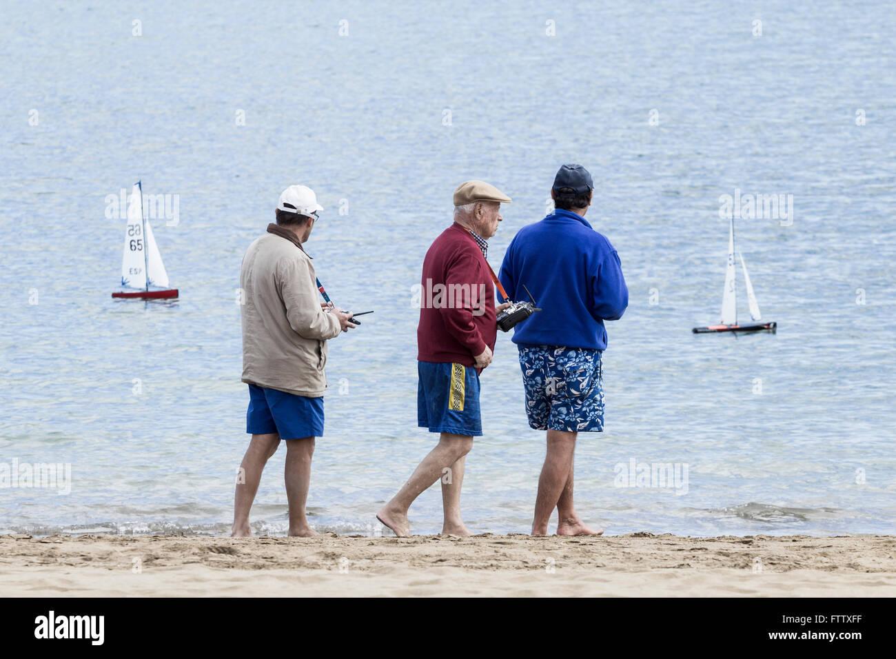 Elderly men in Spain walking along beach racing radio controlled yachts. - Stock Image