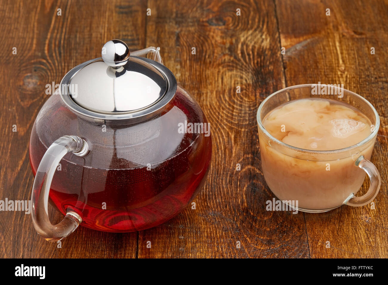 Set of glass teapot and teacup of black tea with milk on wooden table Stock Photo