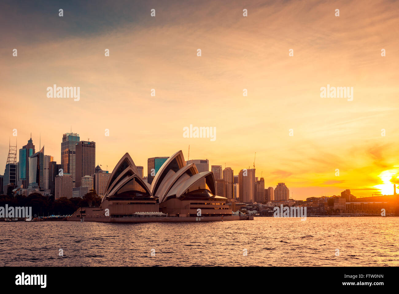 Sydney, Australia - November 11, 2015:  Opera House with Sydney city bihind at sunset. View from the ferry. - Stock Image