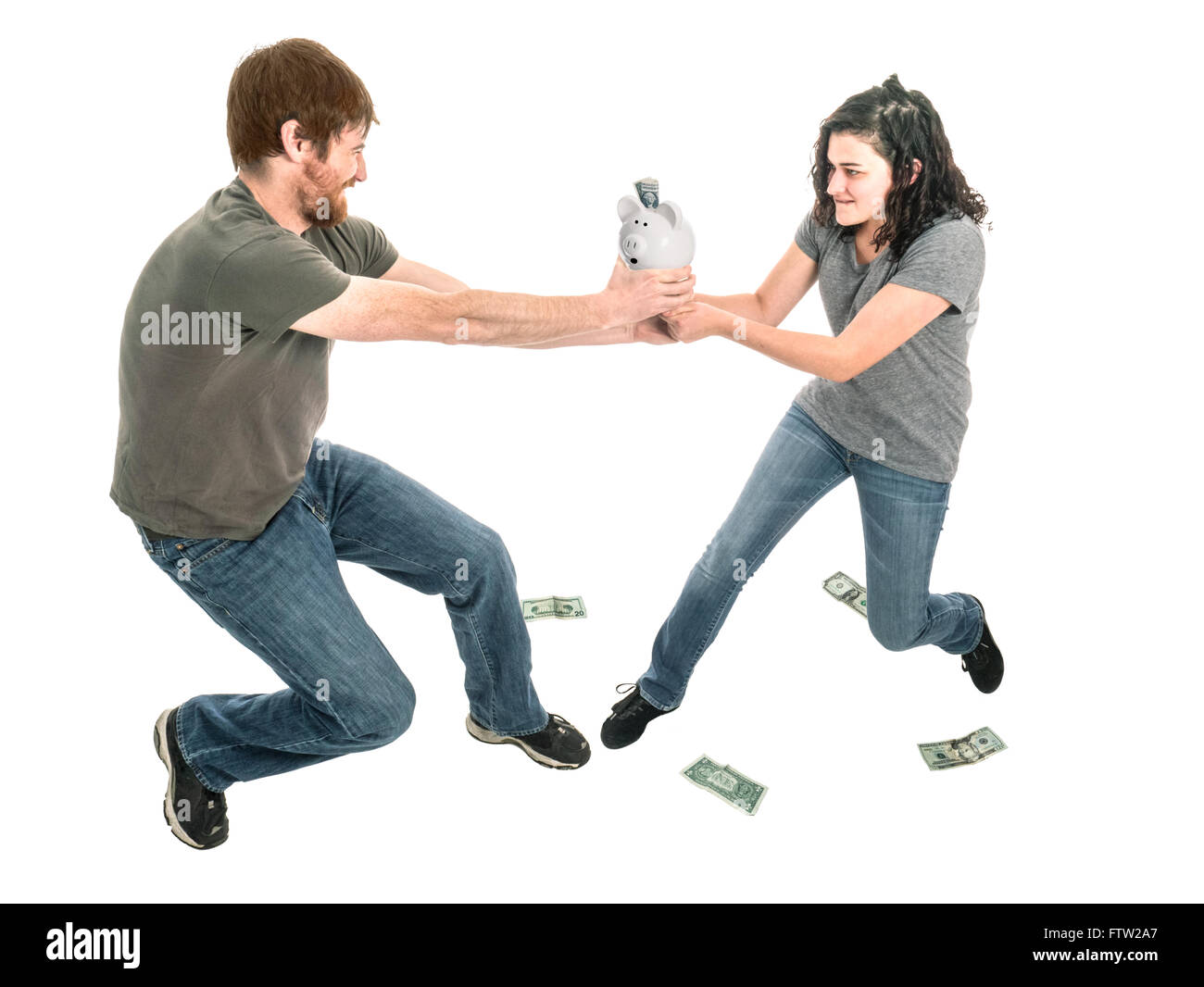 Photograph of a young heterosexual couple engaged in a tug-of-war over control of the piggy bank. - Stock Image