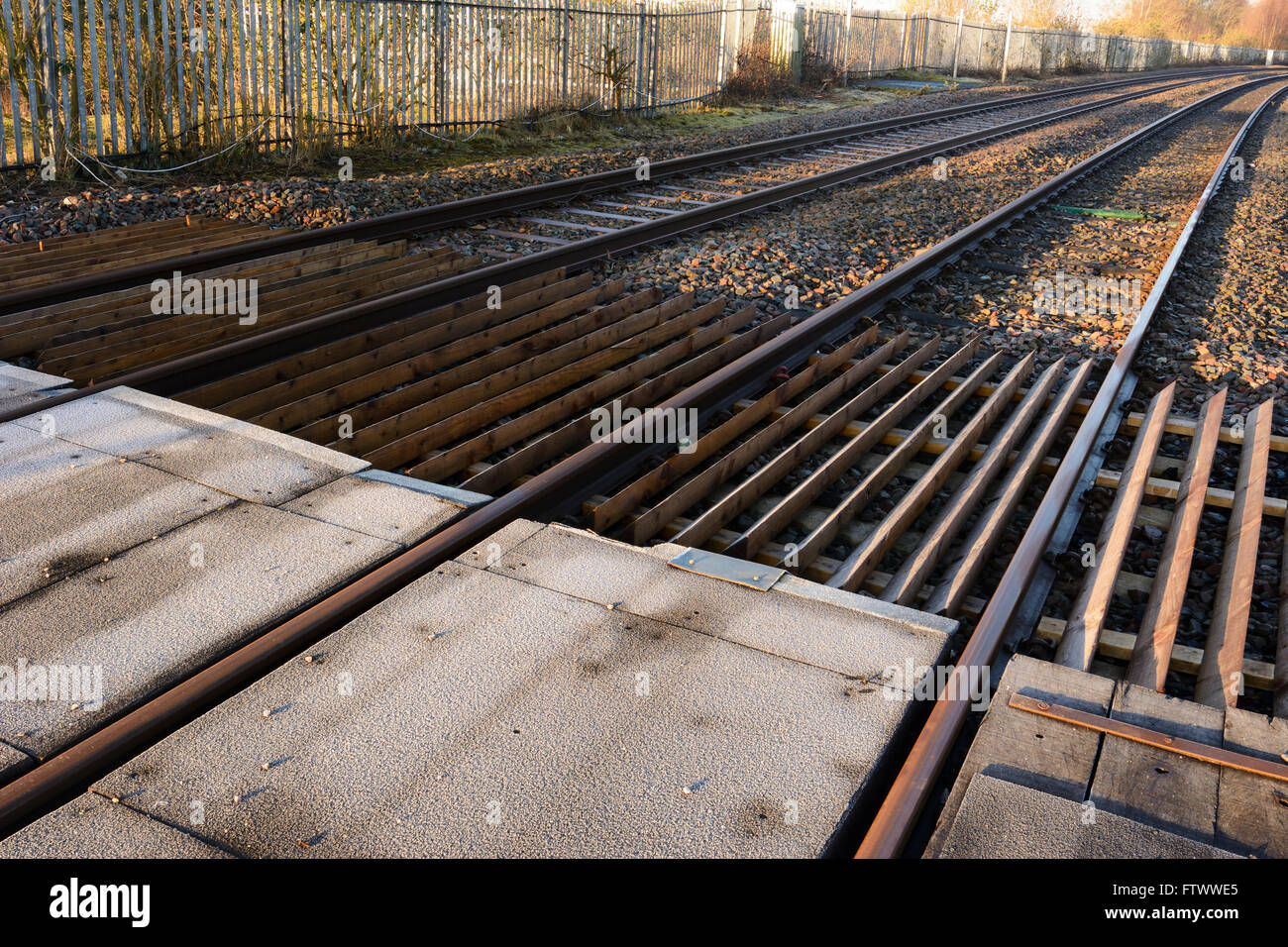 Level crossing and railway lines in early morning light. - Stock Image