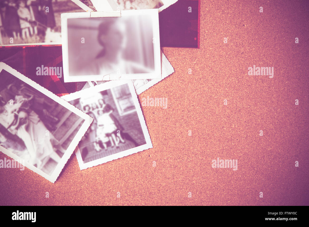 Vintage image of family photographs on corkboard - Stock Image