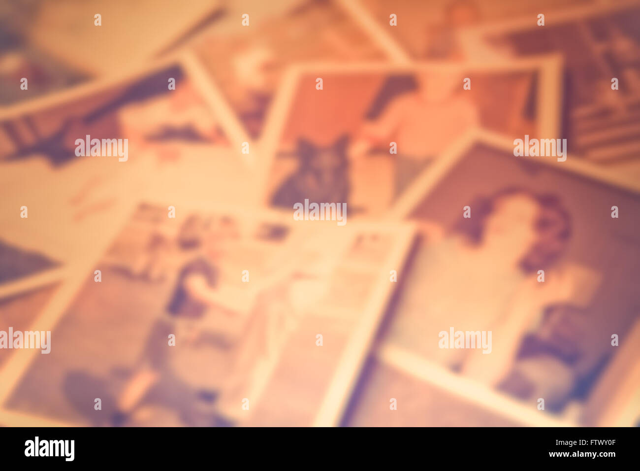 Defocused blur of scattered old family photographs against cork board - Stock Image