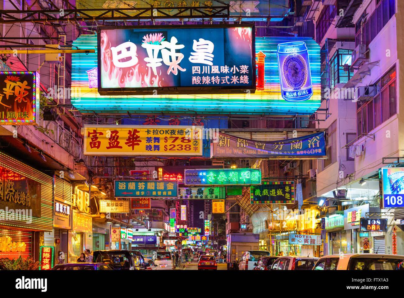Signs illuminate the night in Kowloon, Hong Kong. - Stock Image