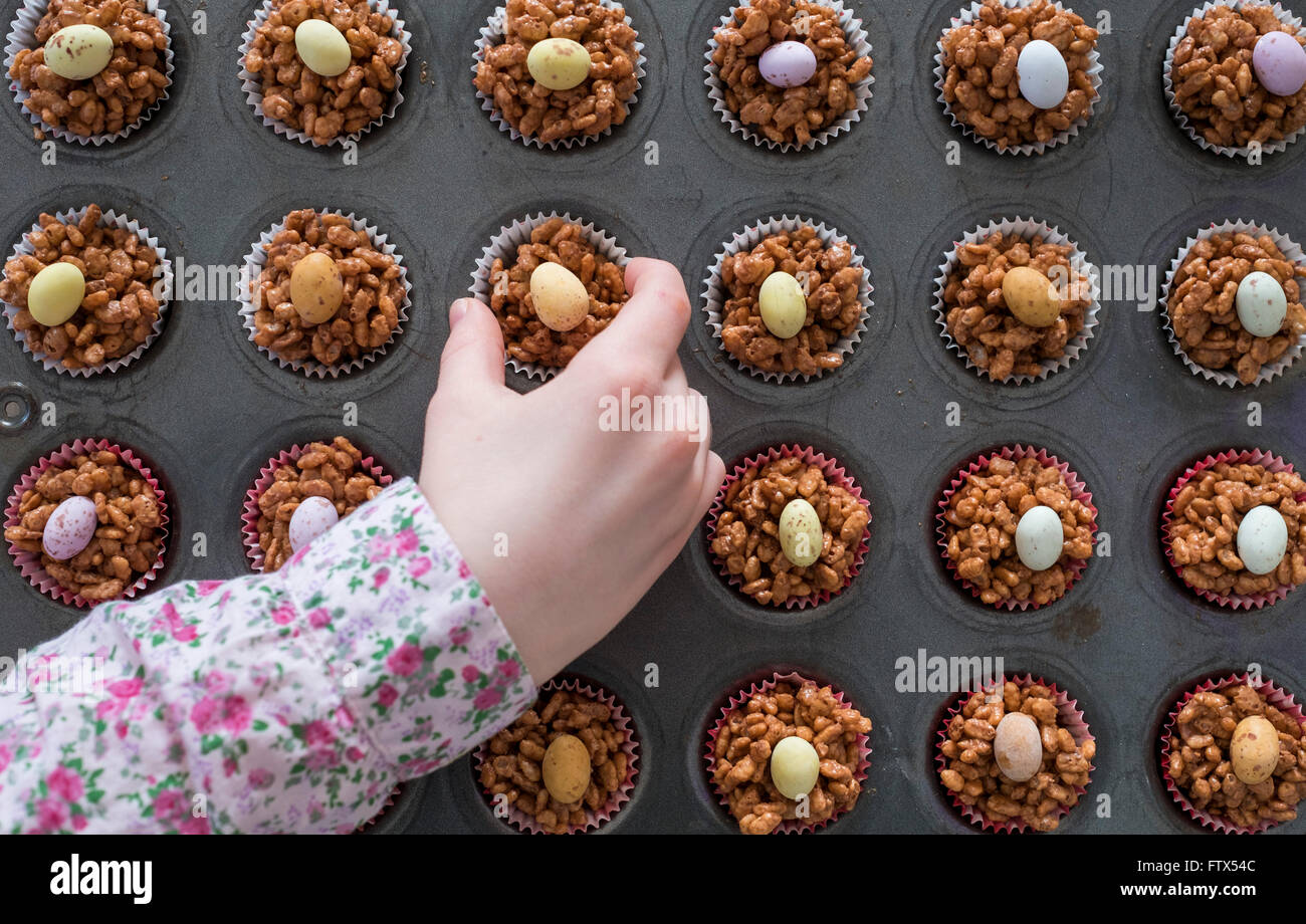A childs hand selecting an Easter chocolate krispy cake - Stock Image