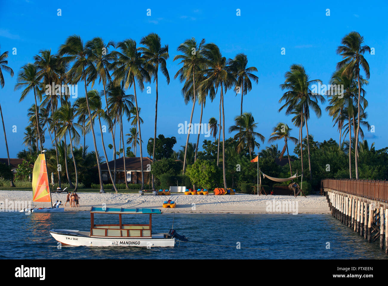 White sandy beach and jetty for the activities below palm trees in front of The Residence Hotel at the Indian Ocean - Stock Image