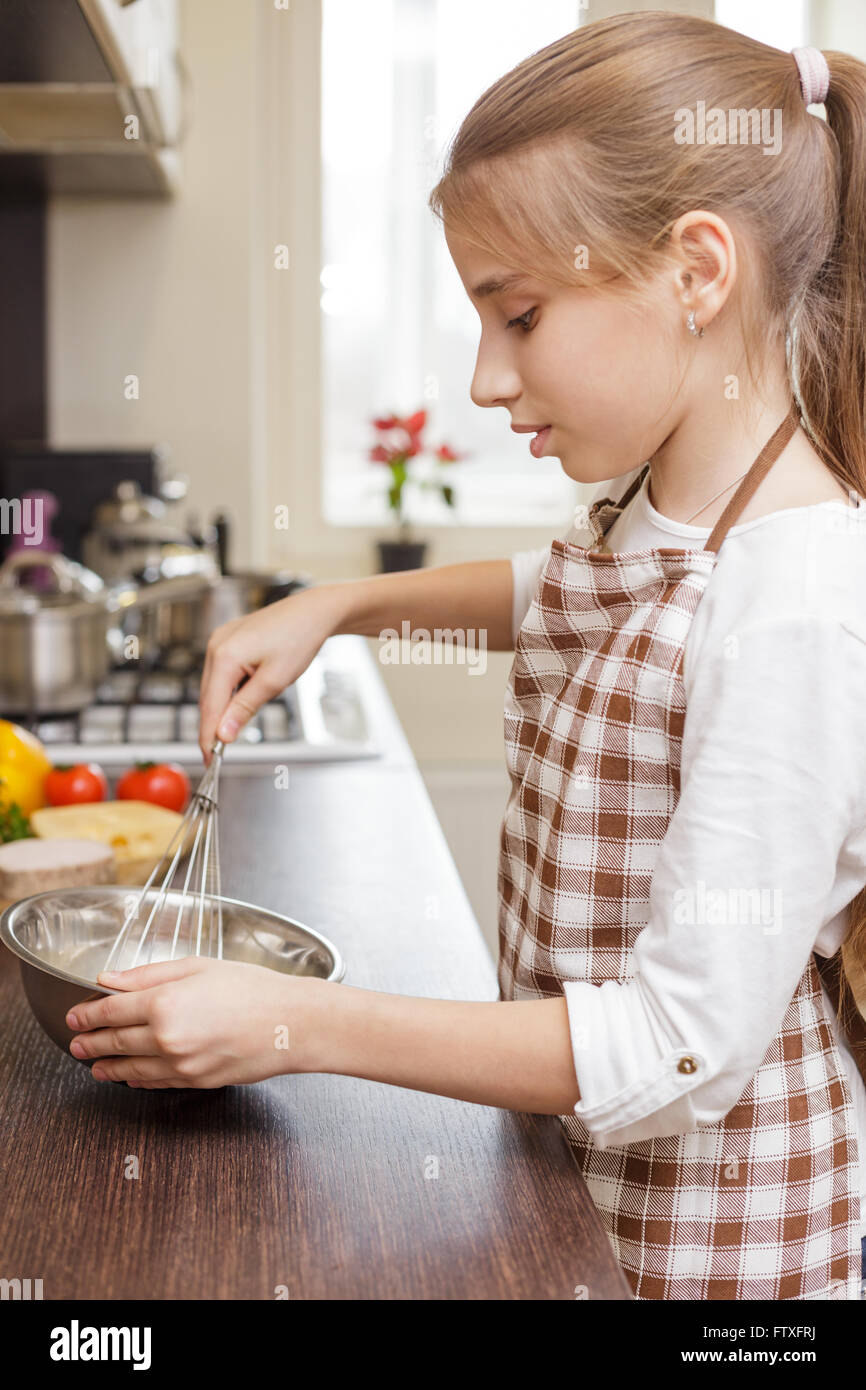 Small teenage girl in apron whisking eggs in white bowl in the kitchen - Stock Image