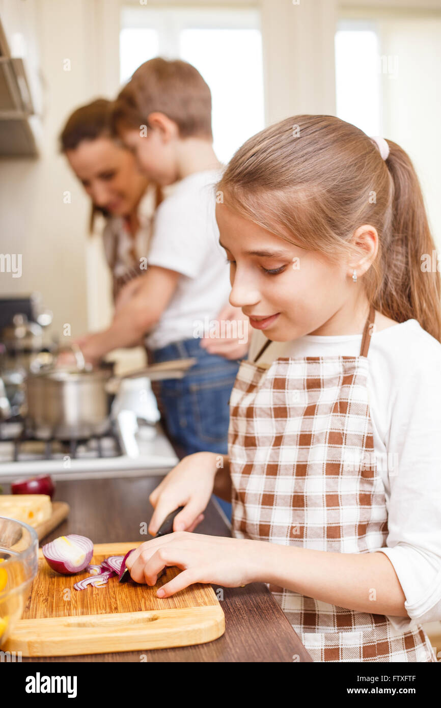 Family cooking background. Young smiling teenage girl cutting onion. Mum and children in the kitchen - Stock Image
