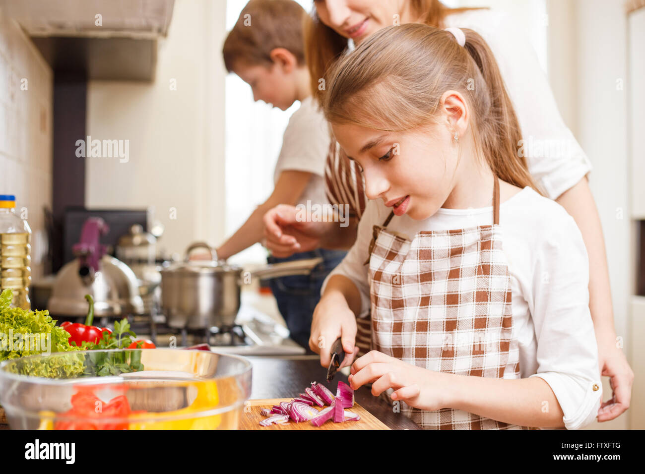 Family cooking background. Mum and daughter cutting onion for salad in the kitchen - Stock Image