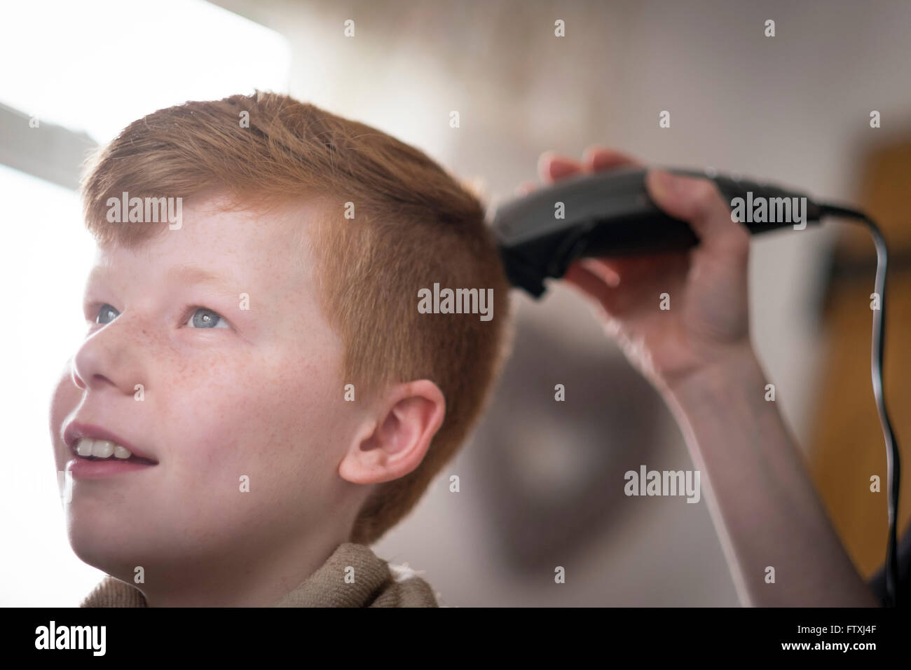 A boy having his hair cut with clippers and scissors. - Stock Image