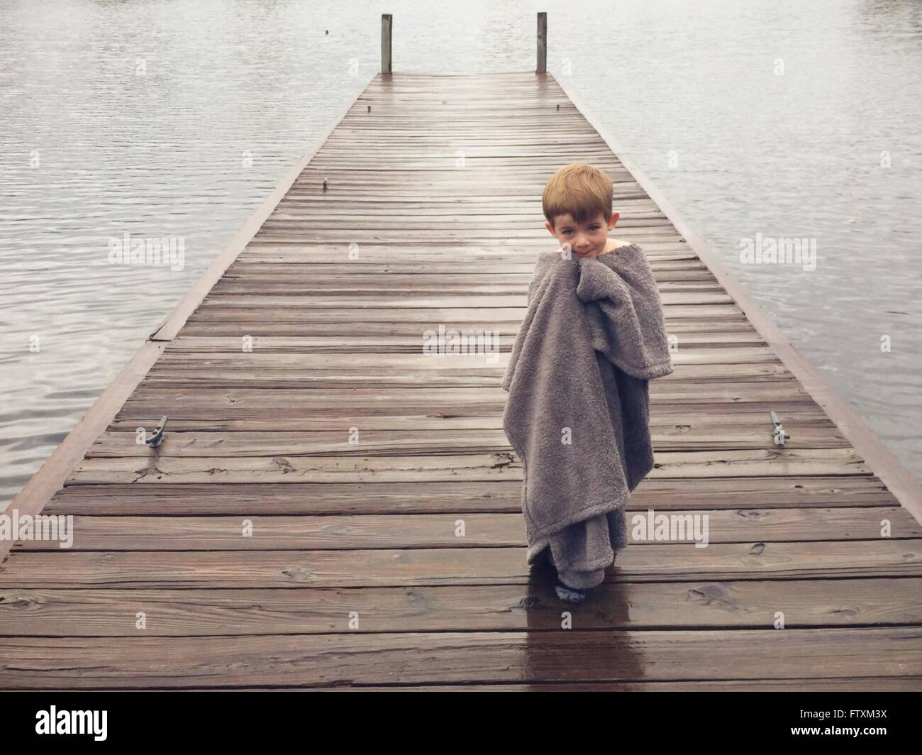 Boy wrapped in blanket, standing on pier - Stock Image