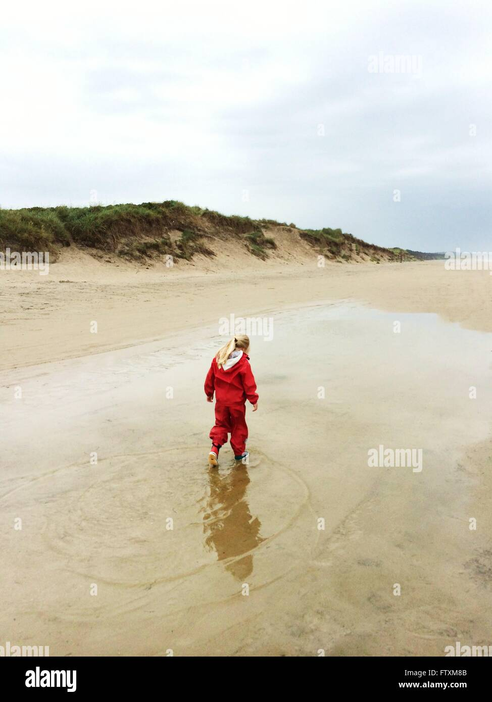 Girl walking on beach on overcast day - Stock Image