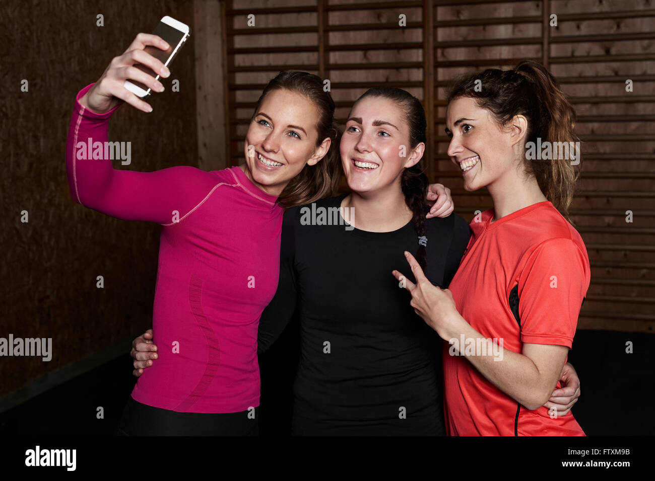 Three young women in gym taking a selfie Stock Photo