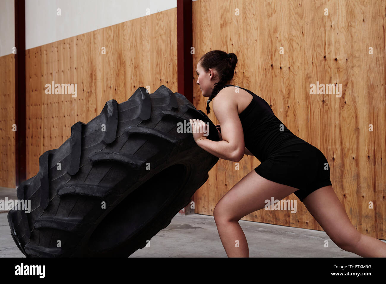 Young woman pushing truck tire in the gym Stock Photo