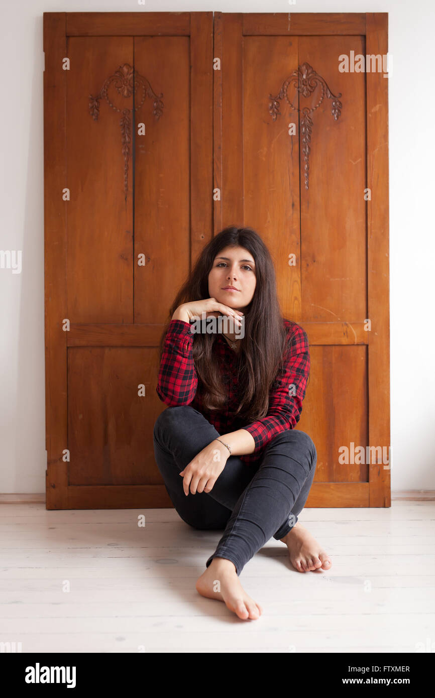 Portrait of a girl sitting on floor in front of wardrobe - Stock Image