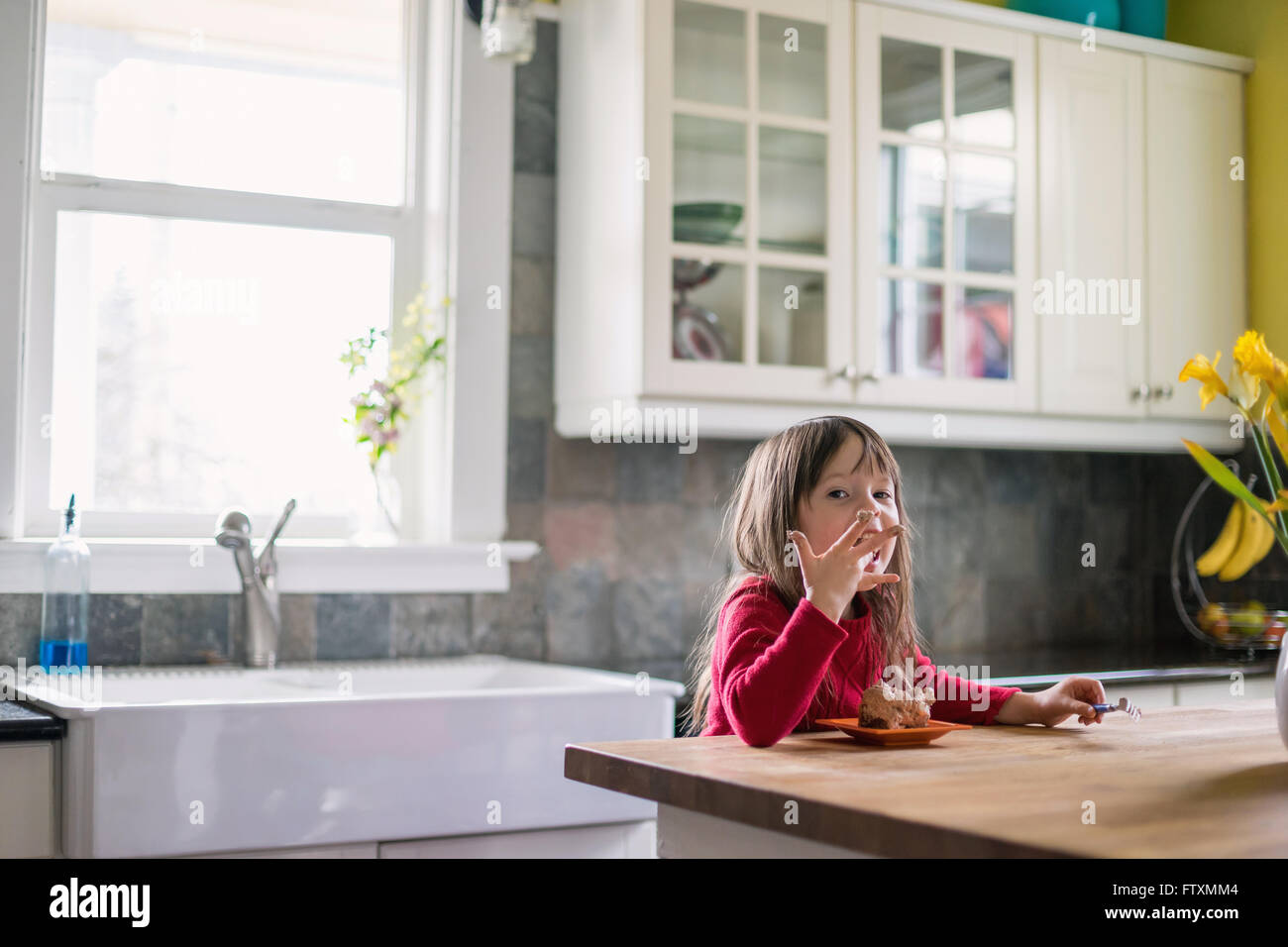 Girl sitting in kitchen eating chocolate dessert and licking fingers - Stock Image