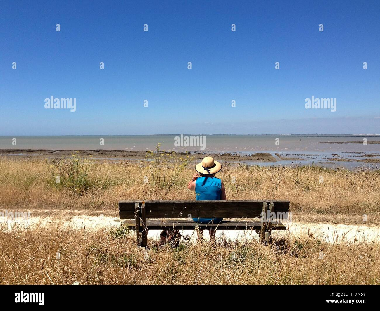 Mature woman sitting on bench by sea, Nieul-sur-Mer, La Rochelle, France - Stock Image
