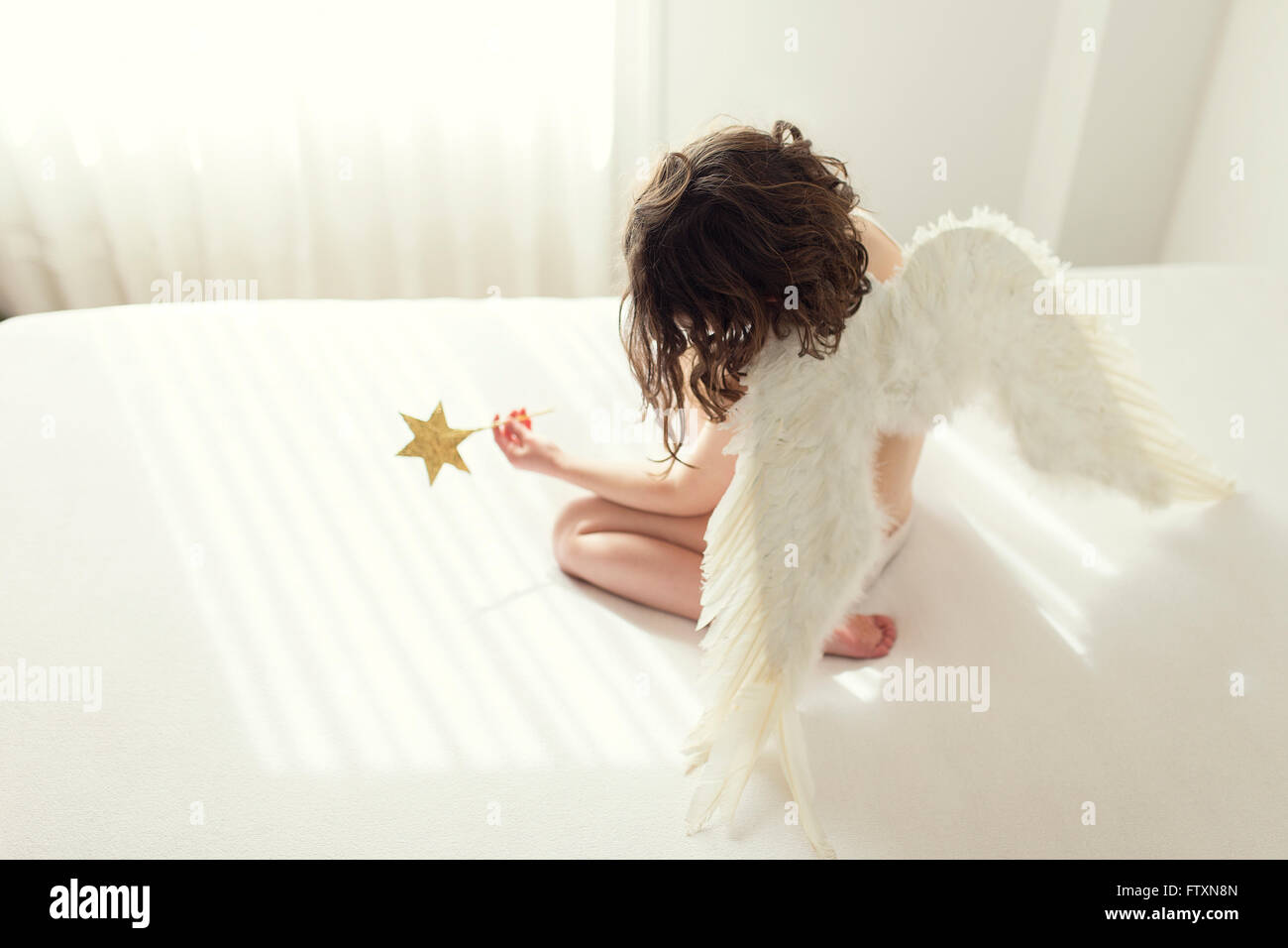 Girl sitting on bed dressed in angel wings holding star wand - Stock Image