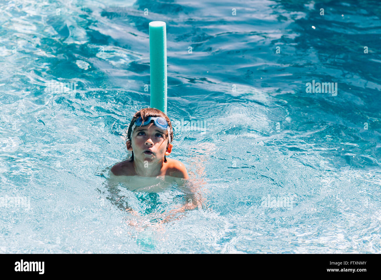 Boy swimming in swimming pool with water noodle Stock Photo