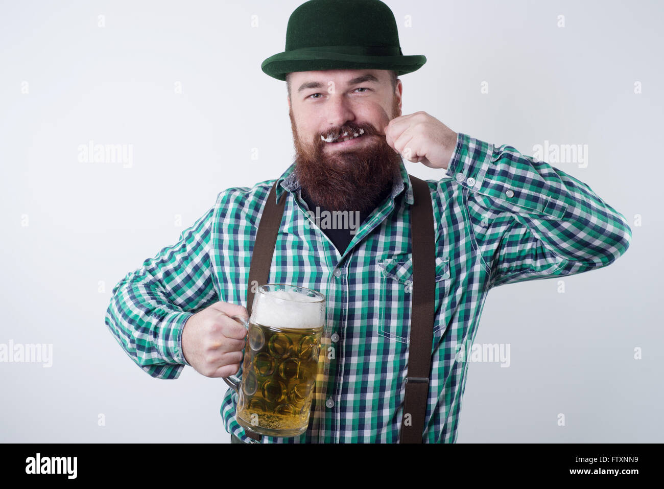 Man holding a beer glass and twirling his moustache - Stock Image