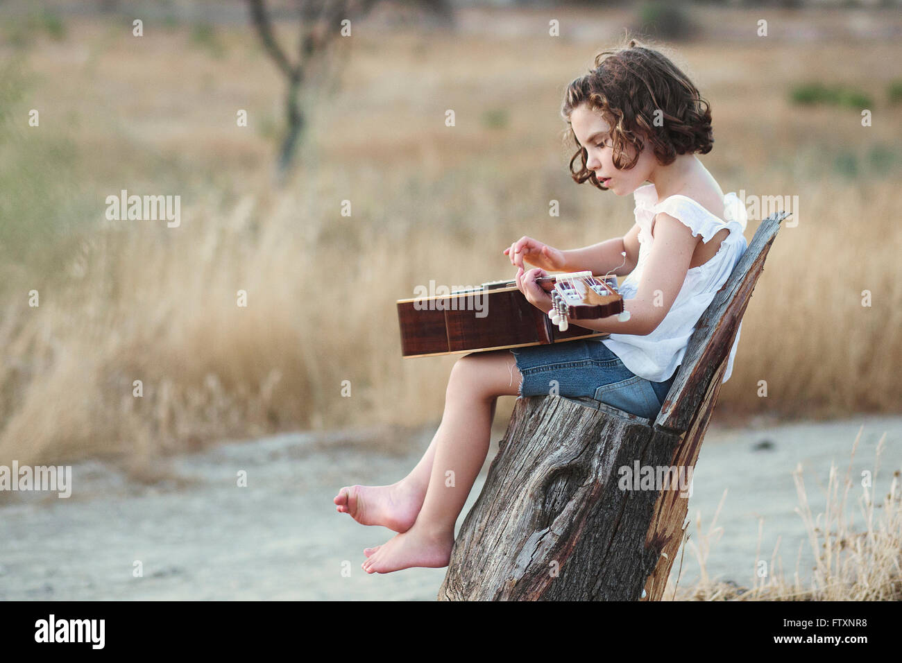 Girl sitting in a field playing the guitar - Stock Image