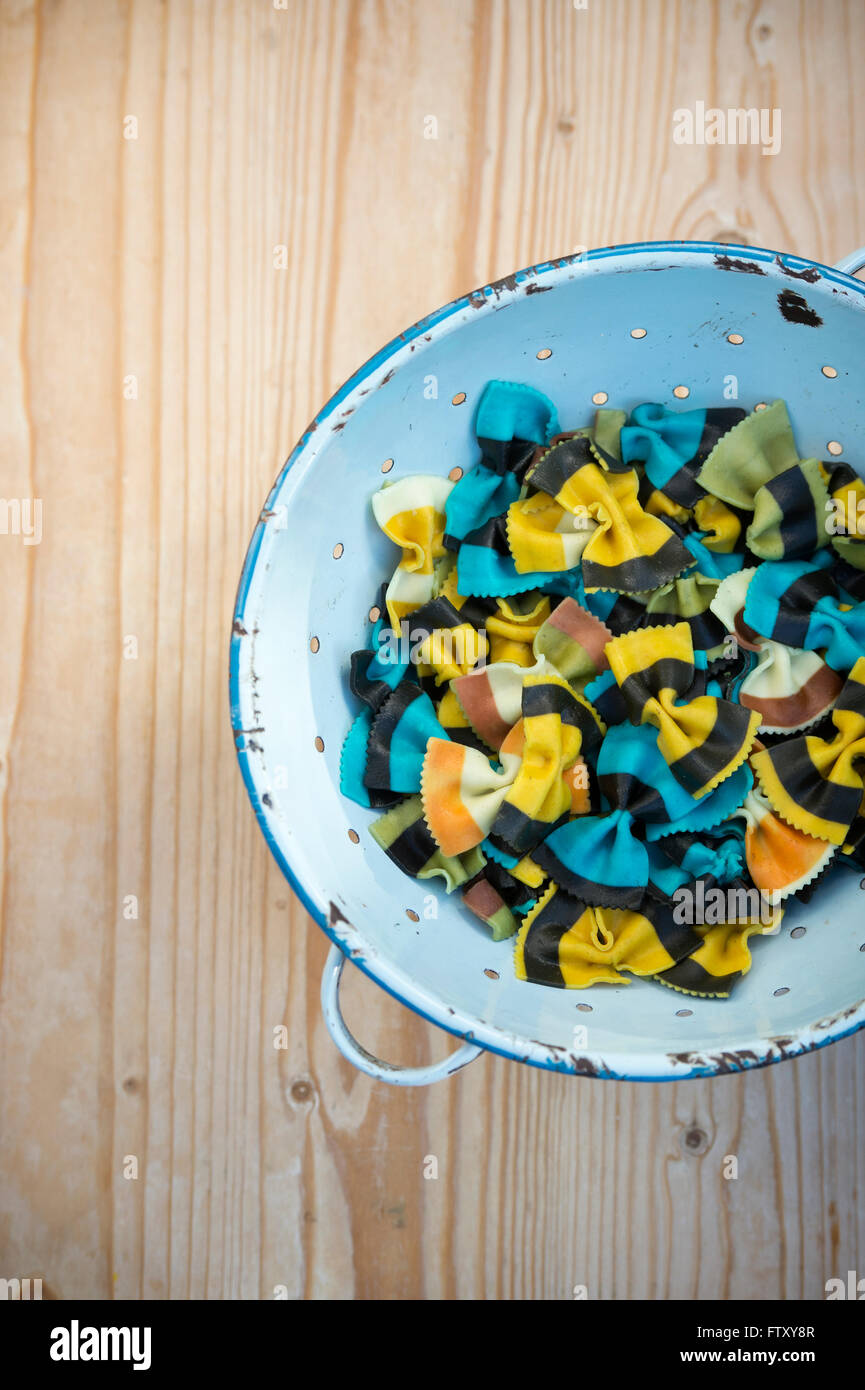 Butterfly Fantasia pasta. Farfalle pasta. Flavored coloured Pasta. Cooked Specialty pasta in a blue retro colander - Stock Image