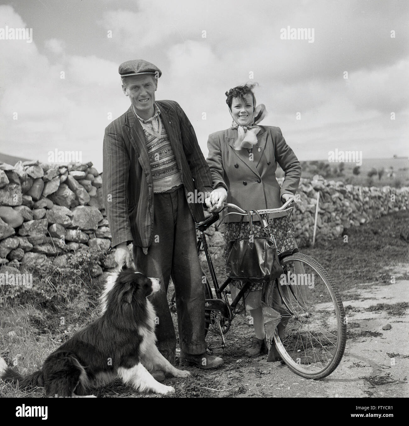 1950s historical, West of Ireland, Irish farmer with sheep dog and wife with bicycle stop on country lane for their - Stock Image