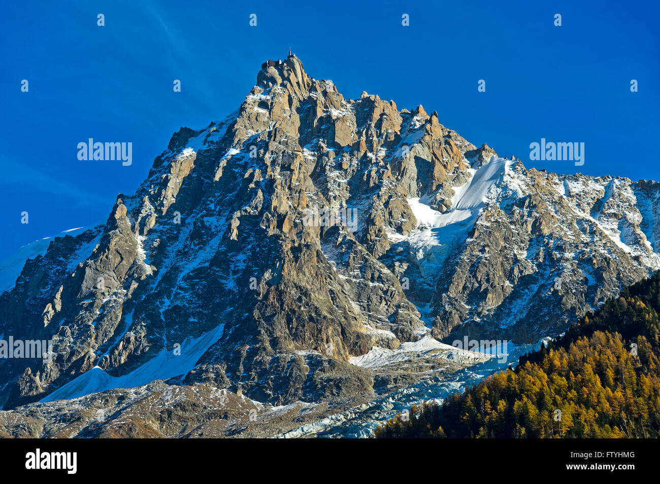 Rocky massif of the Aiguille du Midi peak with upper cable car station, Chamonix, Haute Savoie, France - Stock Image