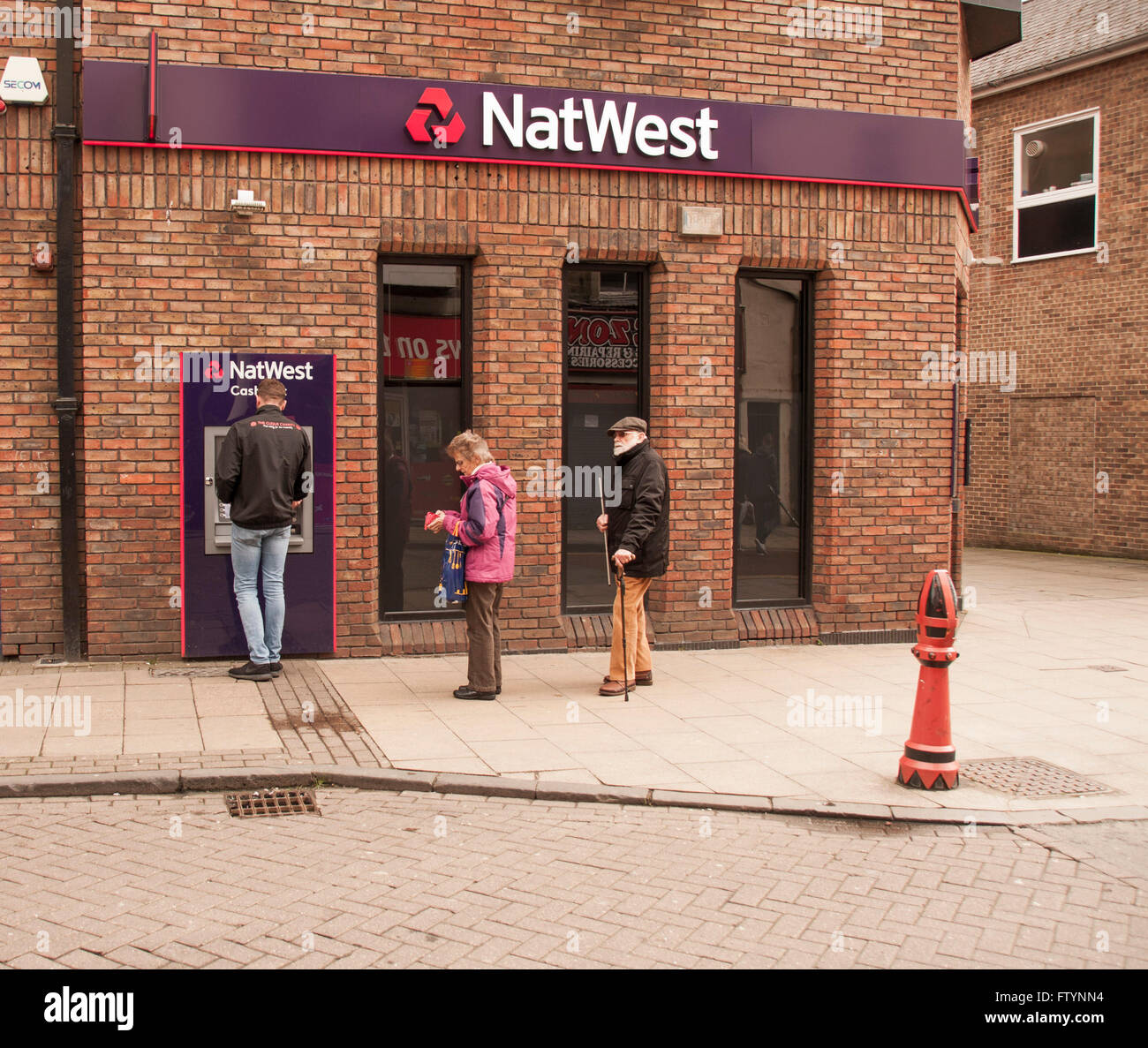 People using or waiting to use the ATM at National Westminster Bank in Bishop Auckland,Co.Durham,England,UK - Stock Image