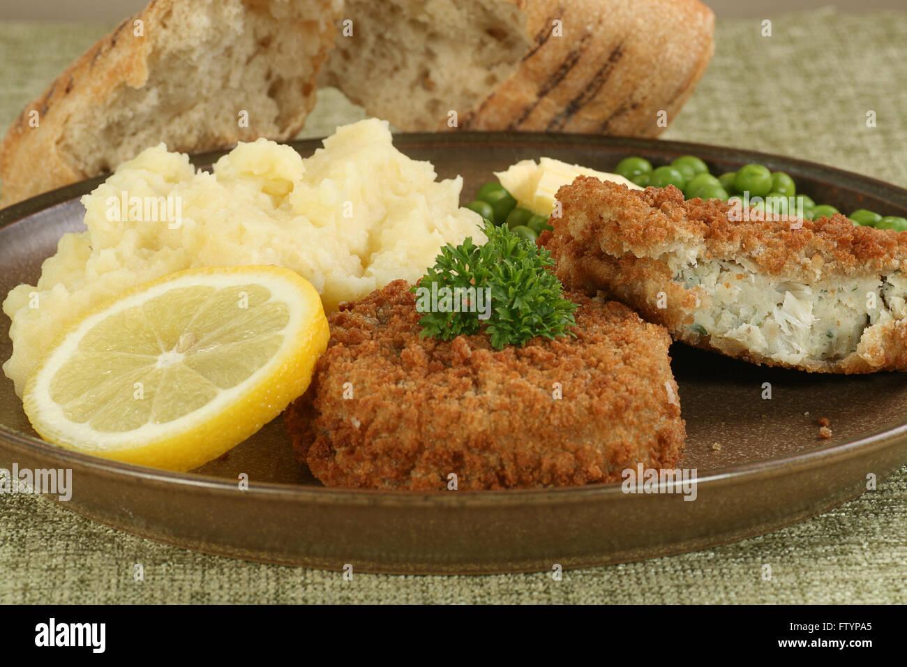 two fresh cod fishcakes with mashed potato and peas - Stock Image