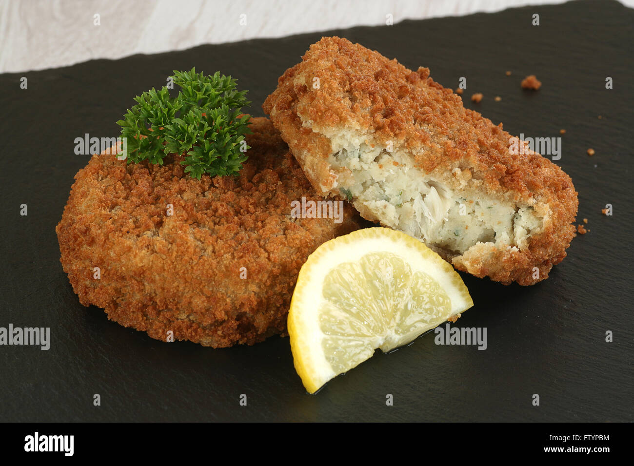 two cod fishcakes with lemon and parsley garnish - Stock Image