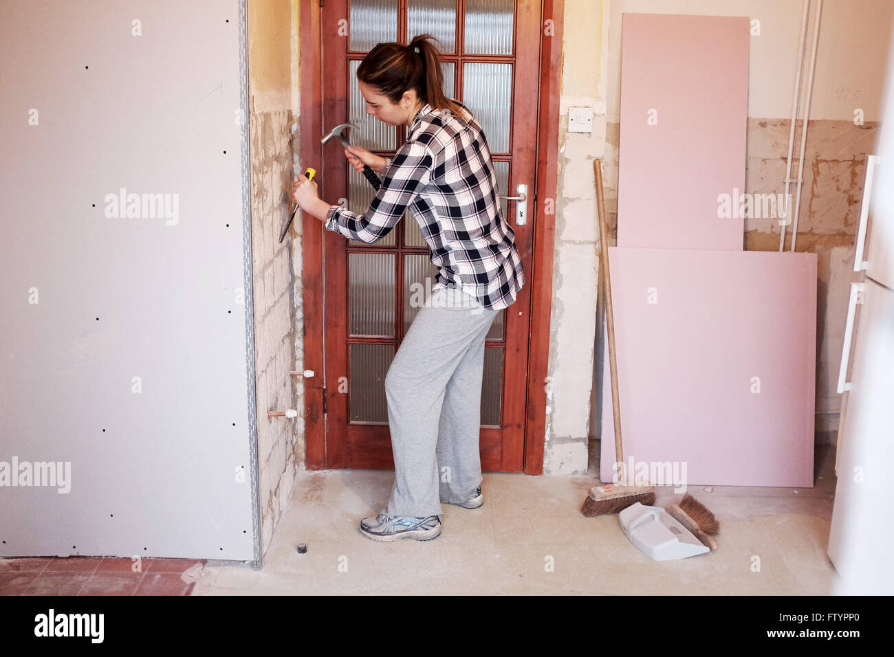 Young woman with hammer and chisel taking off wall tiles in kitchen ...