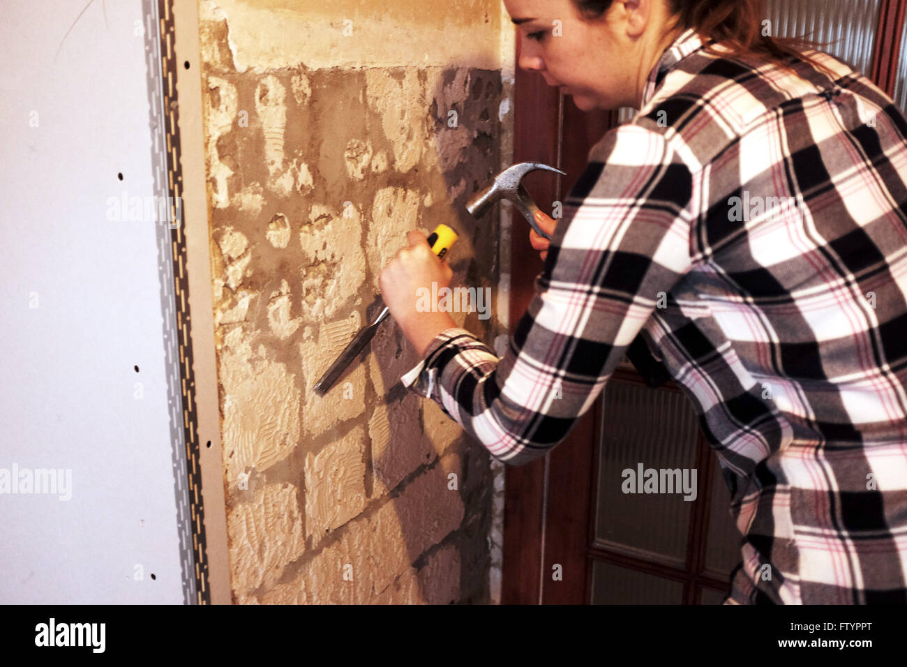 Good Young Woman With Hammer And Chisel Taking Off Wall Tiles In Kitchen In Her  20s Doing DIY At Her Bungalow Home
