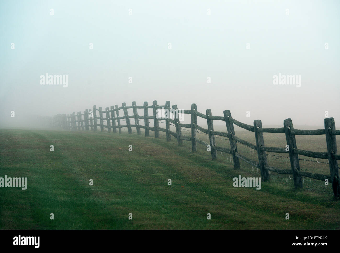 Wooden farm fence on a foggy morning, Connecticut, USA - Stock Image