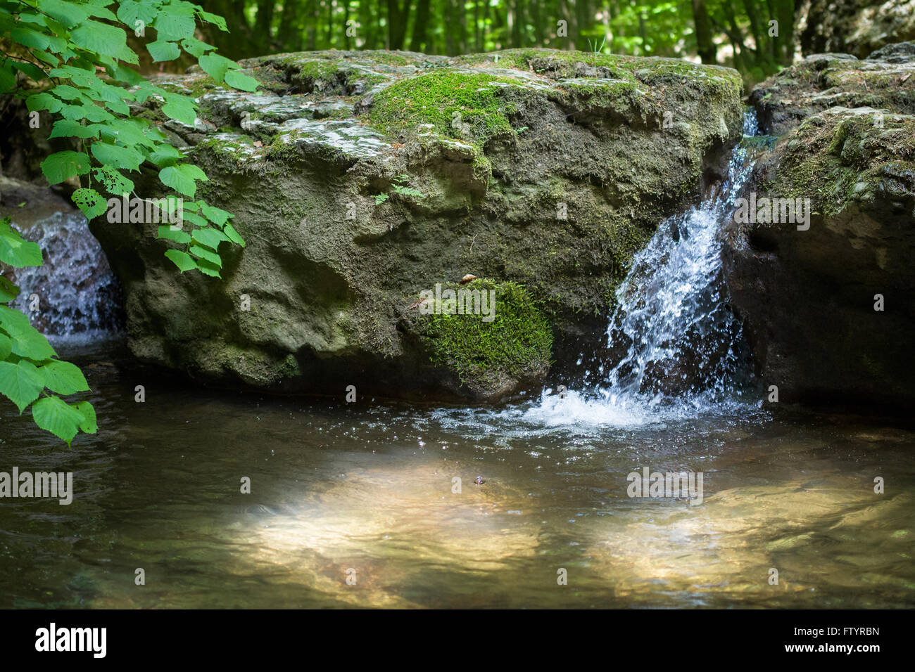 Small waterfall in forest with sun shining through water. - Stock Image