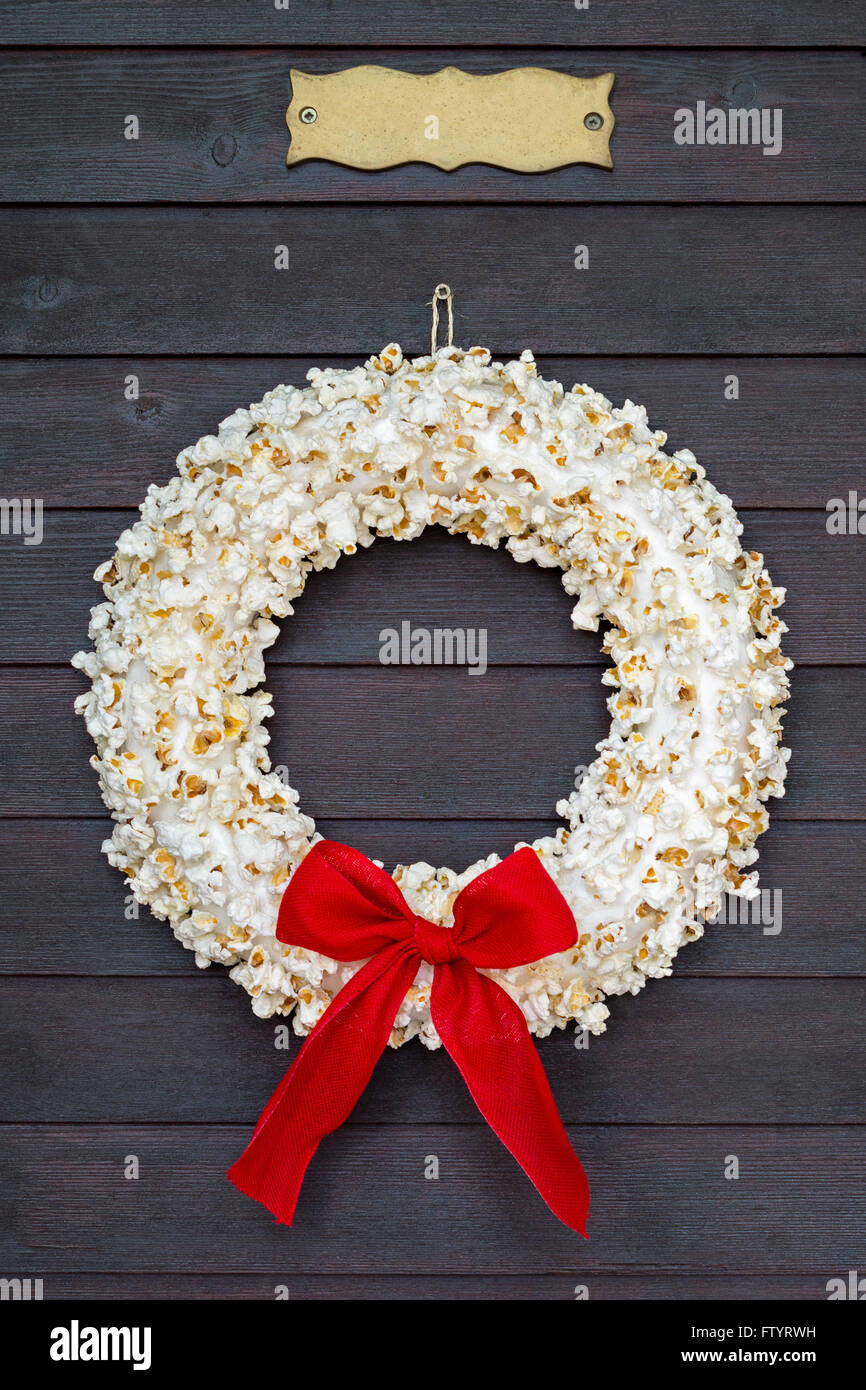 Popcorn wreath with red bow hanging on dark wooden door with name plate. - Stock Image