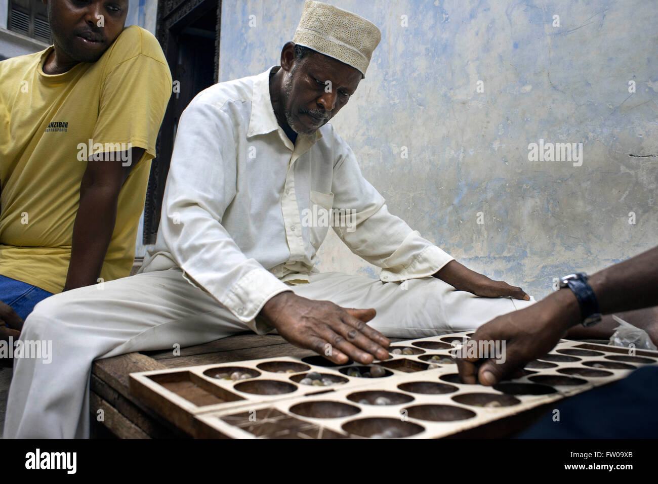 Bao players in Stone Town, Zanzibar. Bao is a traditional mancala board game played in most of East Africa including - Stock Image