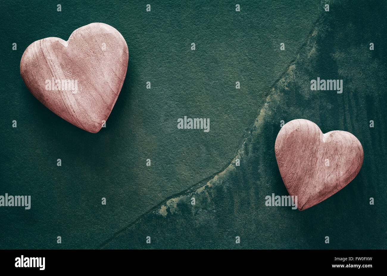 Retro stylized two wooden hearts on cracked stone background, copy space. - Stock Image