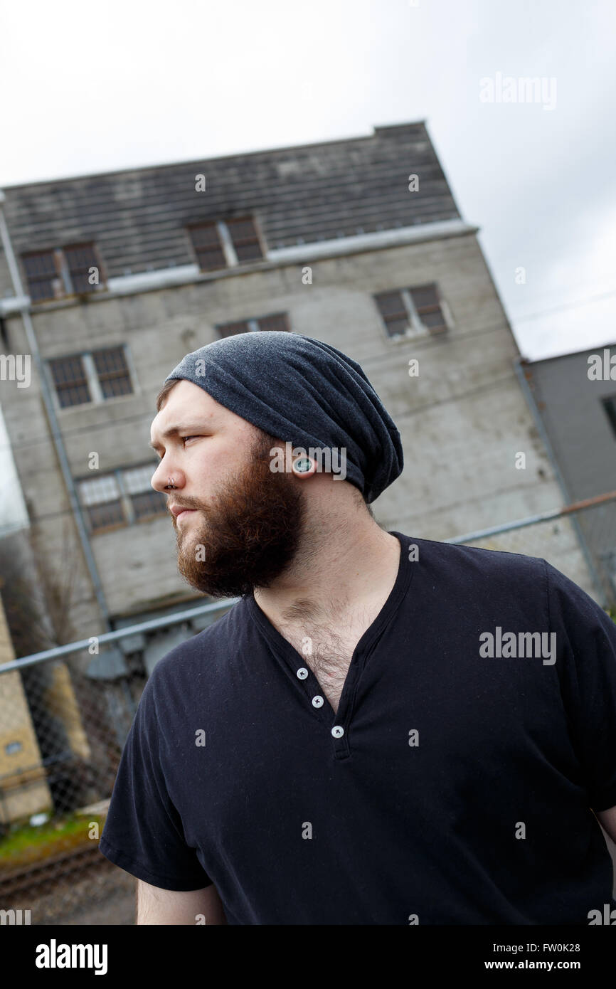 Young adult man outdoors in an urban environment for a lifestyle portrait of a bearded hipster. - Stock Image