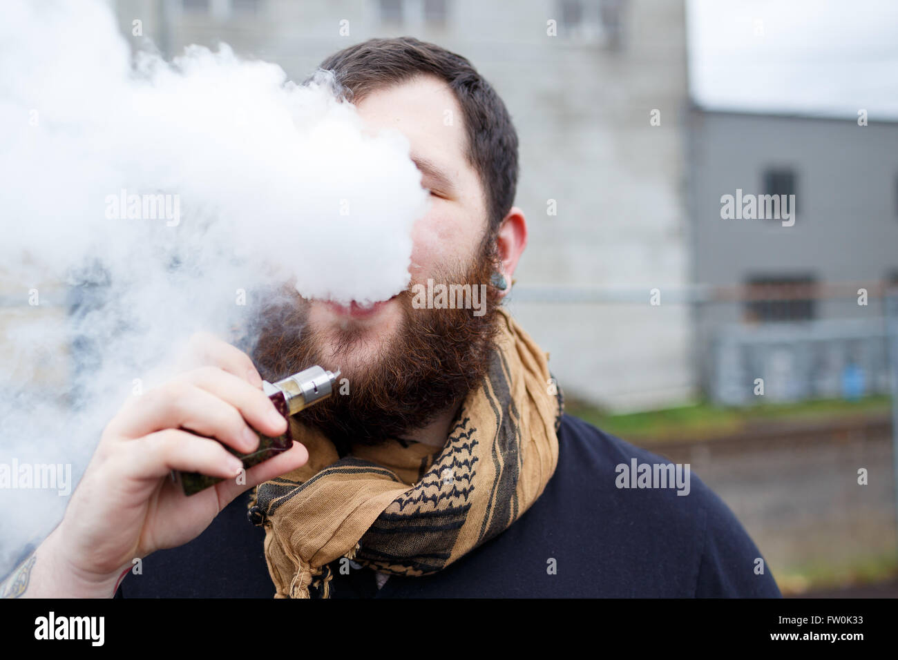 Urban lifestyle portrait of a man vaping in an urban environment with a custom vape mod device. - Stock Image