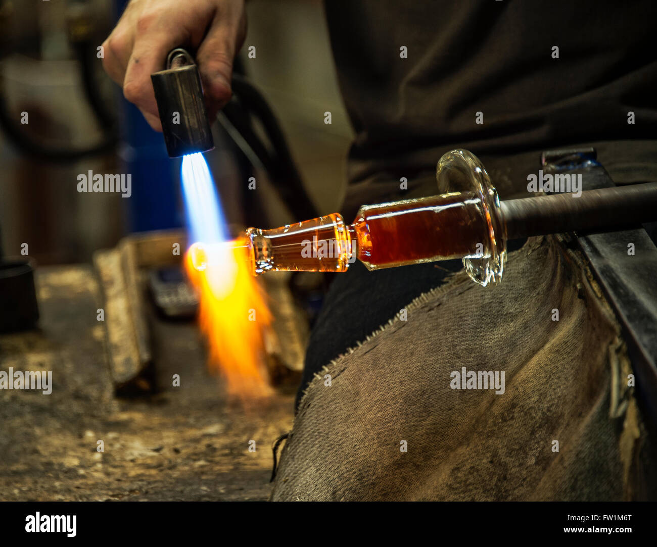 Glass artisan uses a hand torch to soften the piece he is working on. - Stock Image