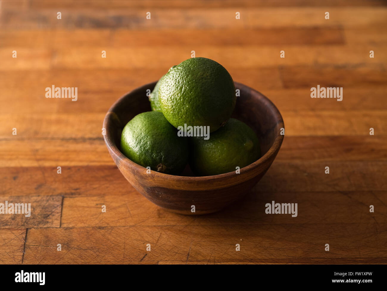 Raw whole limes in bowl on rustic wood - Stock Image
