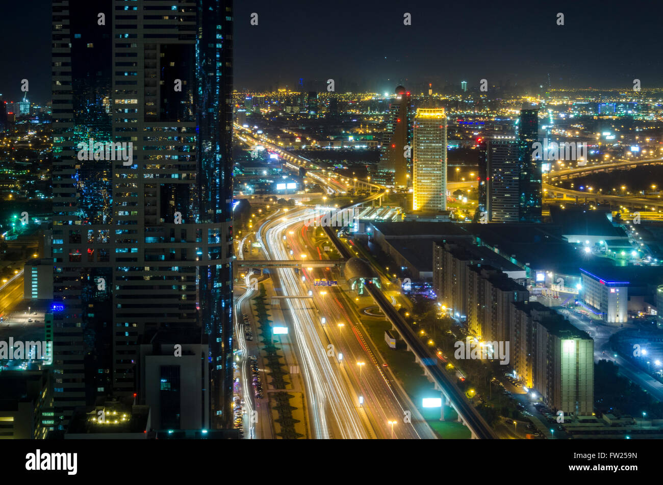 Dubai at night looking East along Sheikh Zayed Road from Emirates Towers Metro Station - Stock Image