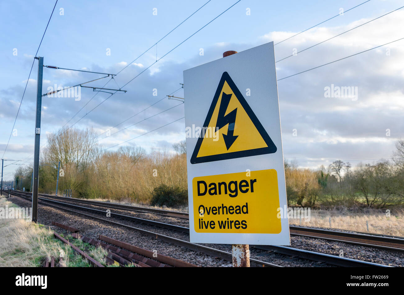 Danger overhead live wires sign next to train tracks - Stock Image