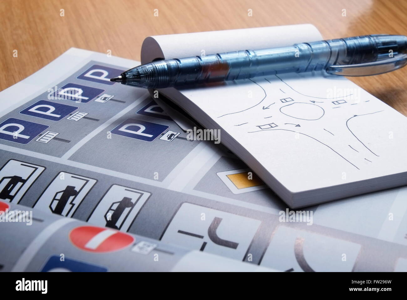 Notepad, book of traffic rules, toy cars, traffic lights and stop sign on a desk table. Studying and preparing for Stock Photo