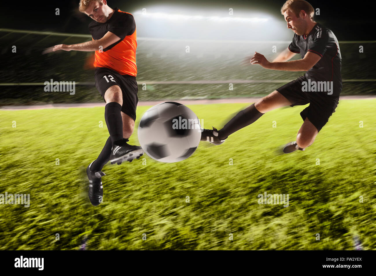Two soccer players kicking a soccer ball - Stock Image