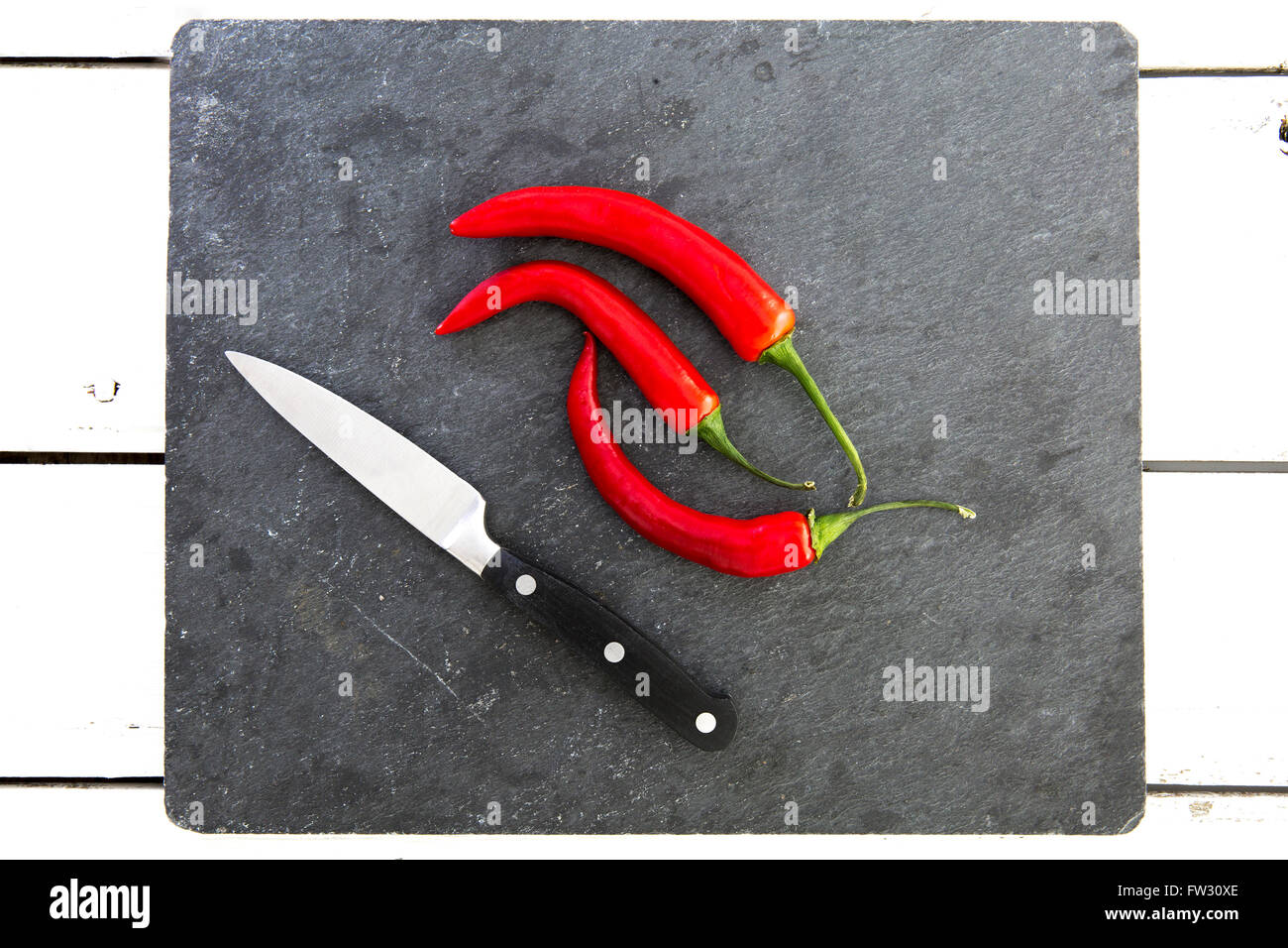 Red chili peppers on slate cutting board with Knife - Stock Image