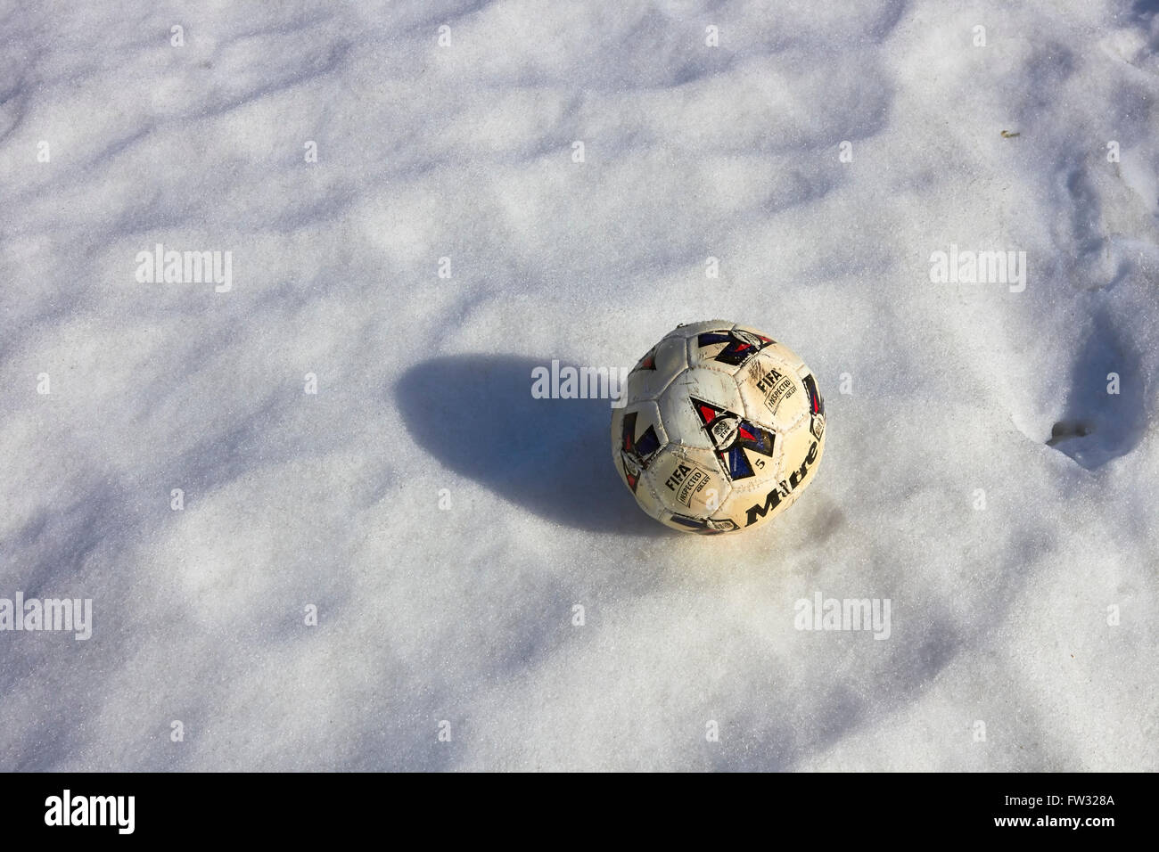 worn-out football on snow - Stock Image