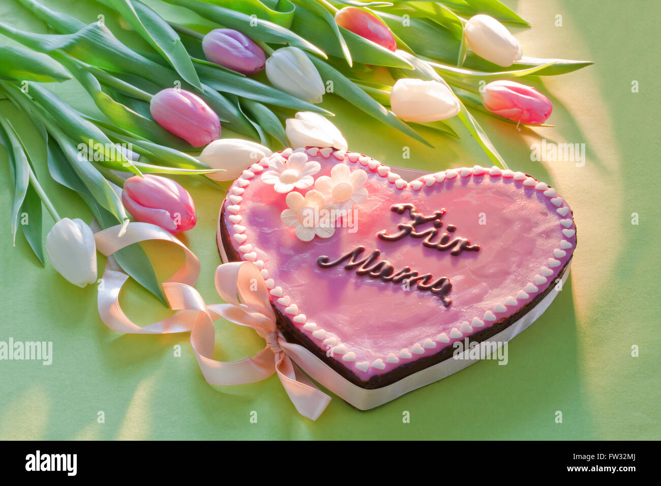 Pink cake with lettering that says Für Mama, For Mum on Mother's Day with flowers - Stock Image