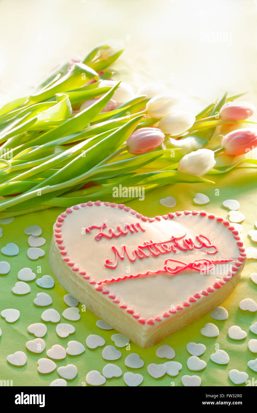 Cake with lettering that says Zum Muttertag, For Mother's Day with flowers - Stock Image